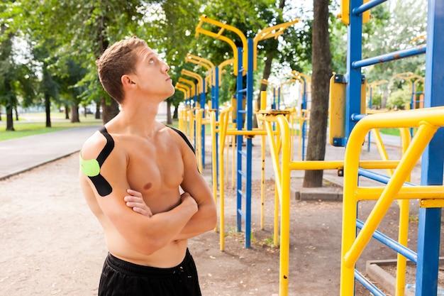 Porträt des schönen jungen kaukasischen professionellen bodybuilders mit schwarzen und grünen elastischen bändern auf den schultern, die am sportplatz aufwerfen.