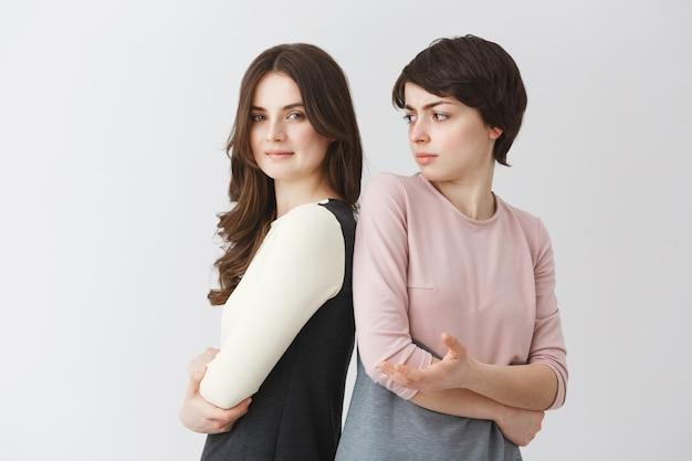 Porträt des schönen jungen lesbischen studentenmädchens mit dem langen haar, das mit der kurzhaarigen kaukasischen freundin in den passenden outfits aufwirft. beziehungskonzept.