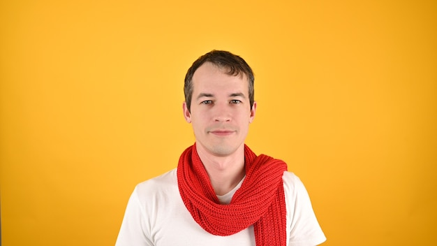 Porträt des schönen jungen mannes im roten schal und im weißen t-shirt. studioaufnahme auf gelbem grund.