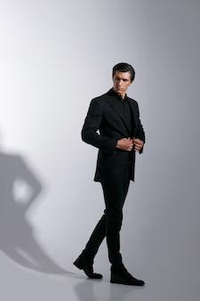 Porträt des schönen jungen mannes im schwarzen stilvollen anzug, lokalisiert auf weißem hintergrund. bild in voller länge.