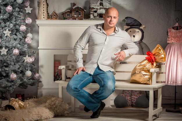 Porträt des schönen jungen mannes im weihnachtsinnenraum