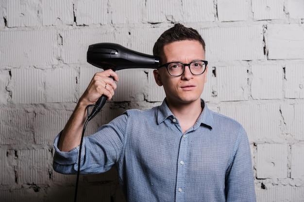 Porträt des schönen jungen mannes in den jeans-kleidern und in den brillen mit dem fön, der zur kamera schaut lächelnd steht und gegen graue backsteinmauer steht