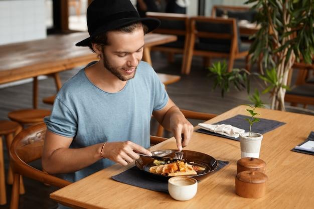 Porträt des schönen jungen mannes mit bart, der glücklich lächelt, während er etwas leckeres essen mit messer und gabel isst