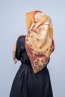 Porträt des schönen jungen modells im modischen hijab-stil, der vor grauem hintergrund posiert