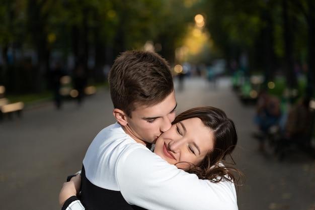 Porträt des schönen jungen paares im park. guy küsste sanft die wange des mädchens.