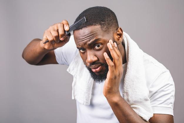 Porträt des schönen jungen schwarzen afroamerikaners, der seine haare im badezimmer kämmt. isoliert über grauem hintergrund. Premium Fotos