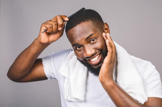 Porträt des schönen jungen schwarzen afroamerikaners, der seine haare im badezimmer kämmt. isoliert über grauem hintergrund.