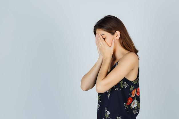 Porträt des schönen jungen weiblichen bedeckenden gesichts mit den händen in der bluse