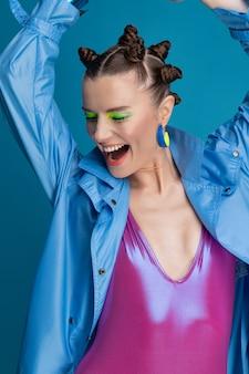 Porträt des schönen jungen weiblichen modells mit neon-make-up und stilvollem haar, das glänzenden badeanzug trägt. lächelndes glückliches mädchen, das im studio aufwirft.