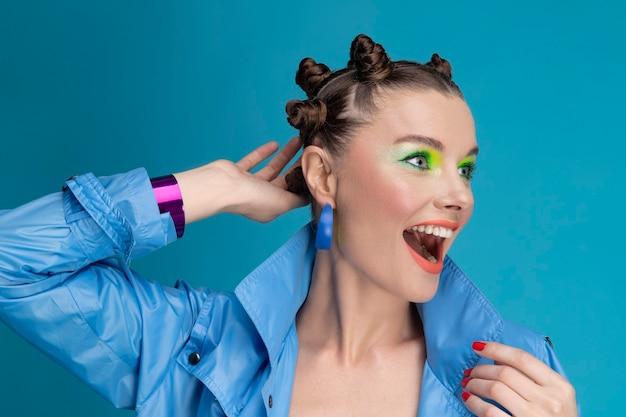 Porträt des schönen jungen weiblichen modells mit neon-make-up und stilvollem haar, das glänzenden blauen mantel trägt. lächelndes überraschtes und glückliches mädchen, das im studio aufwirft.