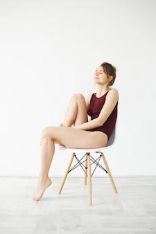 Porträt des schönen jungen zarten modells in der burgunderfarbenen badebekleidung lächelnd posierend im stuhl über weißer wand sitzend.