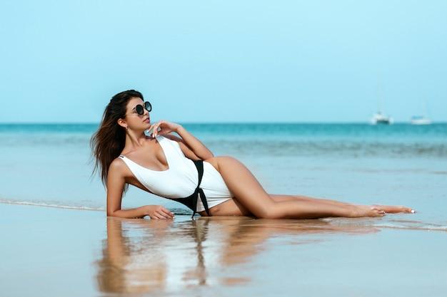 Porträt des schönen kaukasiers nahm frauenmodell in einem weißen badeanzug ein sonnenbad