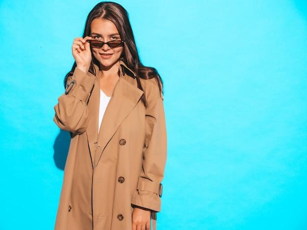 Porträt des schönen kaukasischen brunettefrauenmodells im braunen mantel und in der sonnenbrille mädchen, das nahe blauer wand aufwirft