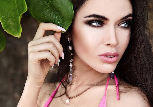 Porträt des schönen kaukasischen frauenmodells mit dem dunklen langen haar im rosa badeanzug, der auf nahe grünem tropischem blatt aufwirft