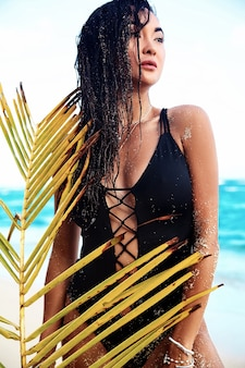 Porträt des schönen kaukasischen frauenmodells mit dem dunklen langen haar im schwarzen badeanzug mit dem palmblatt, das auf sommerstrand mit weißem sand auf blauem himmel und ozean aufwirft