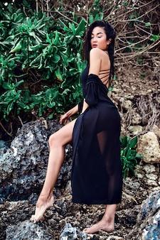 Porträt des schönen kaukasischen frauenmodells mit dem dunklen langen haar in der schwarzen sommerstrandkleidung, die nahe felsen auf sommerstrand aufwirft