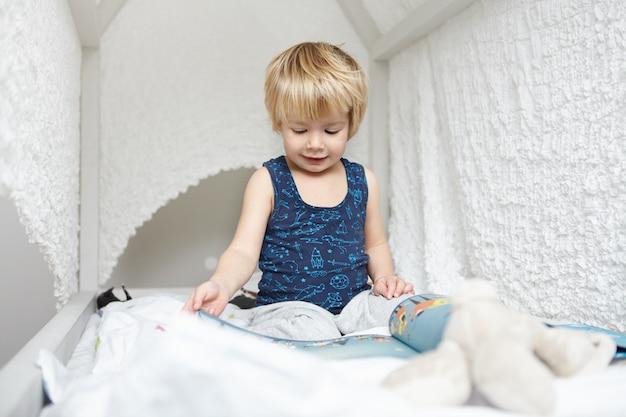 Porträt des schönen kaukasischen jungen mit hellem haar gekleidet im schlafanzug, der auf weißem himmelbett sitzt, absorbiert im lesen des kinderbuches, blick durch bilder mit interessiertem ausdruck