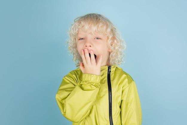 Porträt des schönen kaukasischen kleinen jungen isoliert auf blauer wand