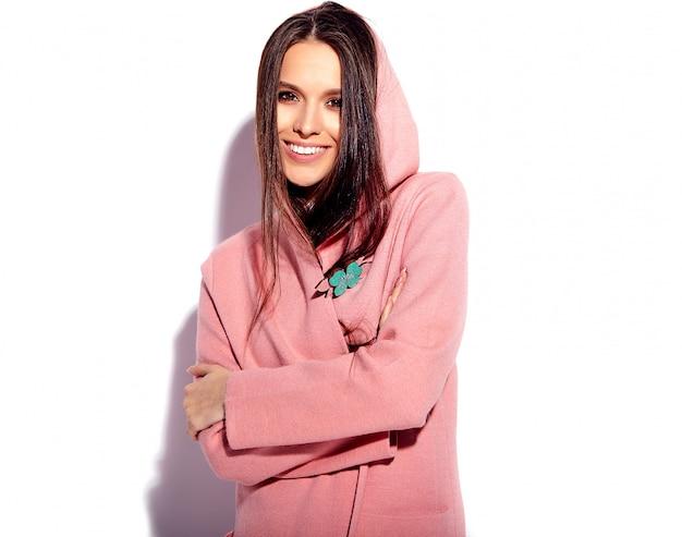 Porträt des schönen kaukasischen lächelnden brunettefrauenmodells im hellen rosa mantel und im stilvollen blauen rock des sommers lokalisiert auf weißem hintergrund