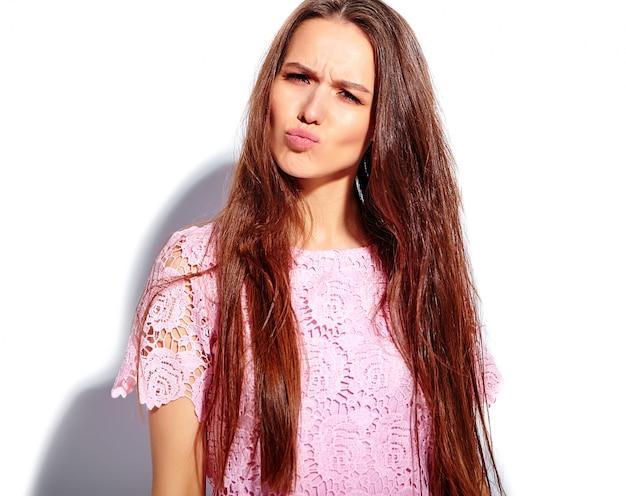 Porträt des schönen kaukasischen lächelnden brunettefrauenmodells im stilvollen kleid des hellen rosa sommers lokalisiert auf weißem hintergrund. ein entengesicht machen