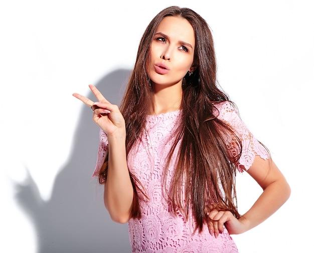 Porträt des schönen kaukasischen lächelnden brunettefrauenmodells im stilvollen kleid des hellen rosa sommers lokalisiert auf weißem hintergrund. zeige friedenszeichen