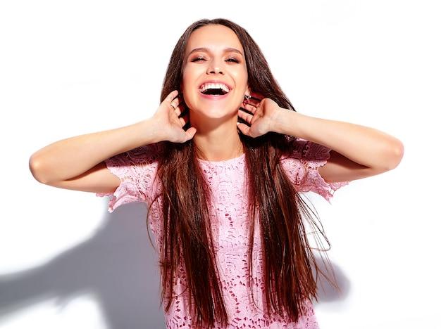 Porträt des schönen kaukasischen lächelnden brunettefrauenmodells im stilvollen kleid des hellen rosa sommers lokalisiert auf weißem hintergrund