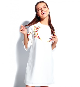 Porträt des schönen kaukasischen lächelnden brunettefrauenmodells im stilvollen kleid des weißen sommers lokalisiert auf weißem hintergrund. sie drehte sich die haare