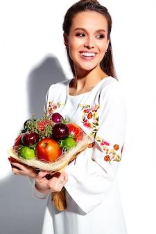 Porträt des schönen kaukasischen lächelnden brunettefrauenmodells im stilvollen kleid des weißen sommers mit ungewöhnlichem kreativem blumenstrauß von blumen
