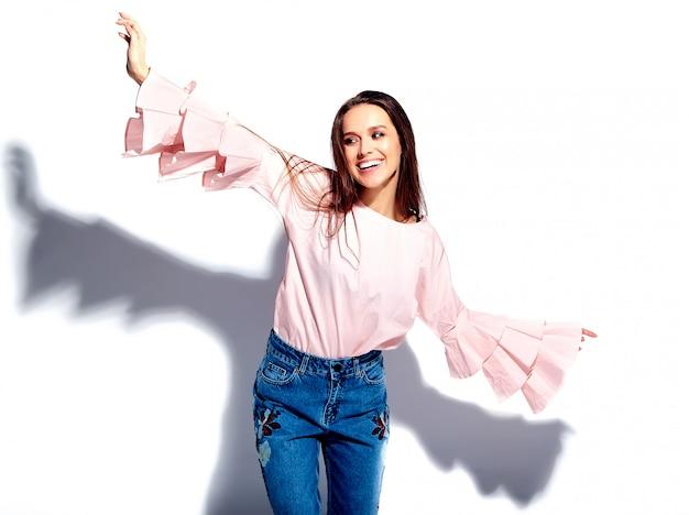 Porträt des schönen kaukasischen lächelnden brunettefrauenmodells in der hellen rosa bluse und in den stilvollen blue jeans des sommers mit blumen drucken