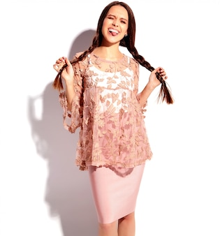 Porträt des schönen kaukasischen lächelnden brunettefrauenmodells in der stilvollen kleidung des hellen rosa sommers lokalisiert auf weißem hintergrund.
