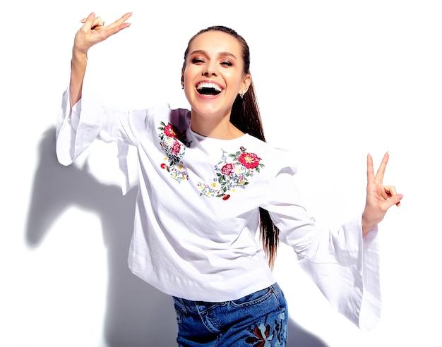 Porträt des schönen kaukasischen lächelnden brunettefrauenmodells in der weißen bluse und in den stilvollen blue jeans des sommers mit blumen drucken