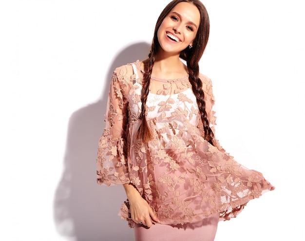 Porträt des schönen kaukasischen lächelnden brunettefrauenmodells mit den doppelten zöpfen in der stilvollen kleidung des hellen rosa sommers
