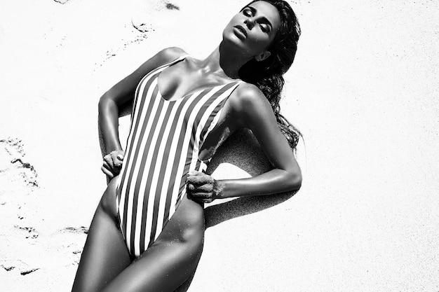 Porträt des schönen kaukasischen modells der sonnengebadeten frau mit dunklem langem haar im gestreiften badeanzug, der auf sommerstrand mit weißem sand aufwirft