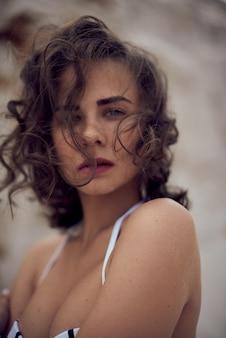 Porträt des schönen kaukasischen sonnenbad-frauenmodells mit dunklem langem haar im gestreiften badeanzug, der auf sommerstrand mit weißem sand liegt. draufsicht