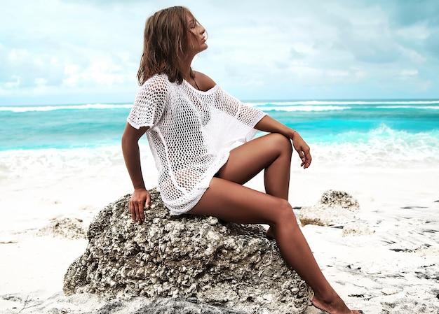 Porträt des schönen kaukasischen sonnengebadeten frauenmodells in der transparenten weißen bluse, die auf sommerstrand und blauem ozeanhintergrund sitzt