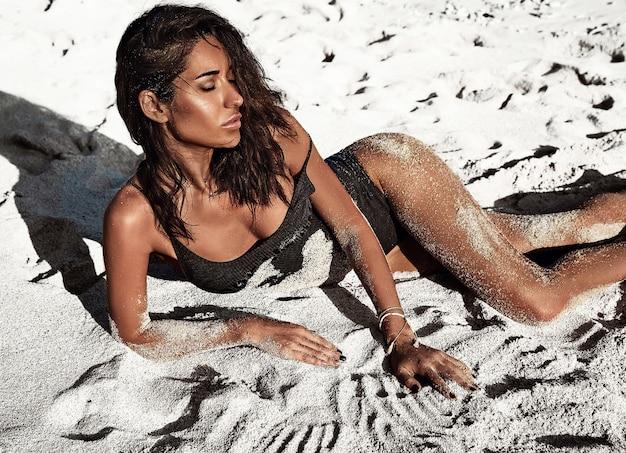 Porträt des schönen kaukasischen sonnengebadeten frauenmodells mit dem dunklen langen haar im badeanzug, der auf sommerstrand mit weißem sand liegt