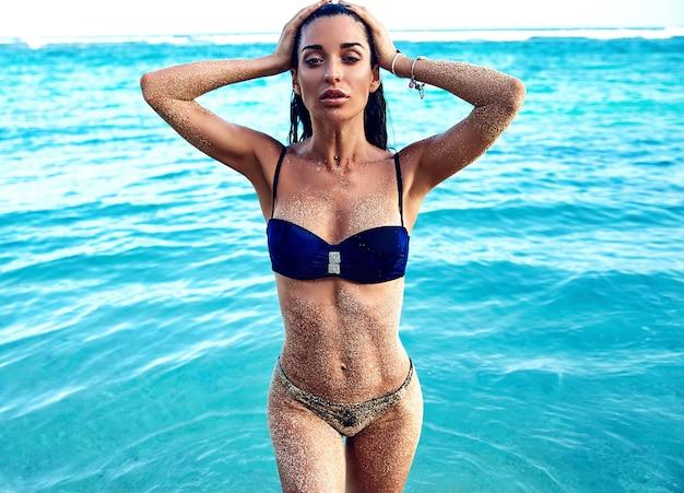 Porträt des schönen kaukasischen sonnengebadeten frauenmodells mit dem dunklen langen haar im badeanzug, der aus blaues ozeanwasser herauskommt