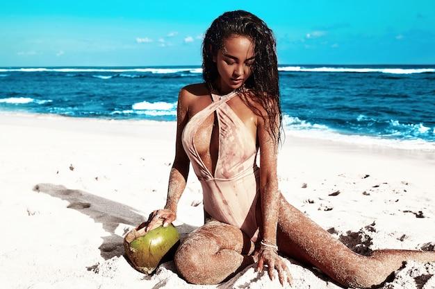 Porträt des schönen kaukasischen sonnengebadeten frauenmodells mit dem dunklen langen haar im beige badeanzug, der auf sommerstrand mit weißem sand auf blauem himmel und ozean aufwirft