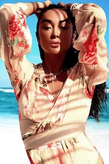 Porträt des schönen kaukasischen sonnengebadeten frauenmodells mit dem dunklen langen haar im beige fliegenkleid, das auf sommerstrand mit weißem sand auf blauem himmel und ozean aufwirft
