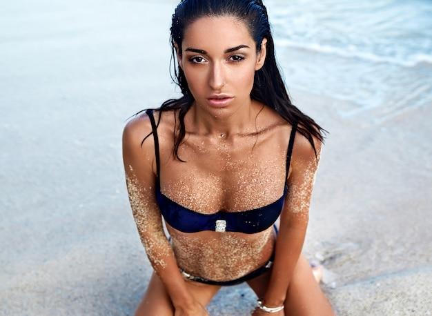 Porträt des schönen kaukasischen sonnengebadeten frauenmodells mit dem dunklen langen haar im dunklen badeanzug, der auf sommerstrand mit weißem sand nahe wasser aufwirft