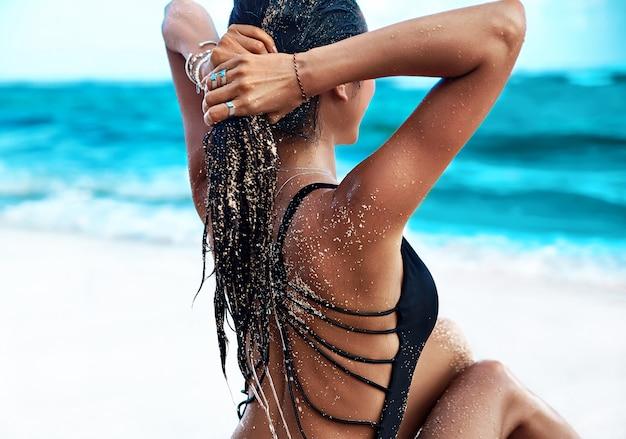Porträt des schönen kaukasischen sonnengebadeten frauenmodells mit dem dunklen langen haar im schwarzen badeanzug, der auf sommerstrand mit weißem sand auf blauem himmel und ozean aufwirft