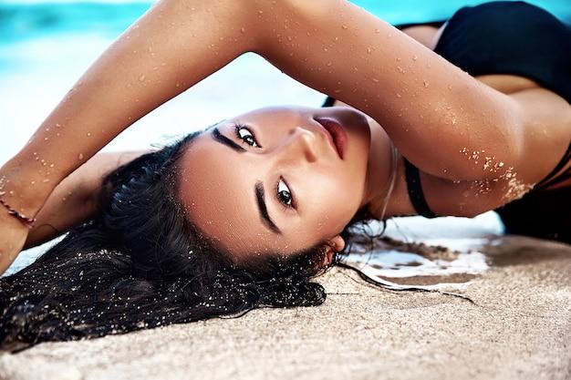 Porträt des schönen kaukasischen sonnengebadeten frauenmodells mit dem dunklen langen haar im schwarzen badeanzug, der auf sommerstrand mit weißem sand auf blauem himmel und ozean liegt