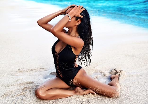 Porträt des schönen kaukasischen sonnengebadeten frauenmodells mit dem dunklen langen haar im schwarzen badeanzug, der auf sommerstrand mit weißem sand auf wand des blauen himmels und des ozeans aufwirft. sie berührte ihre haare