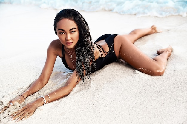 Porträt des schönen kaukasischen sonnengebadeten frauenmodells mit dem dunklen langen haar im schwarzen badeanzug, der auf sommerstrand mit weißem sand liegt
