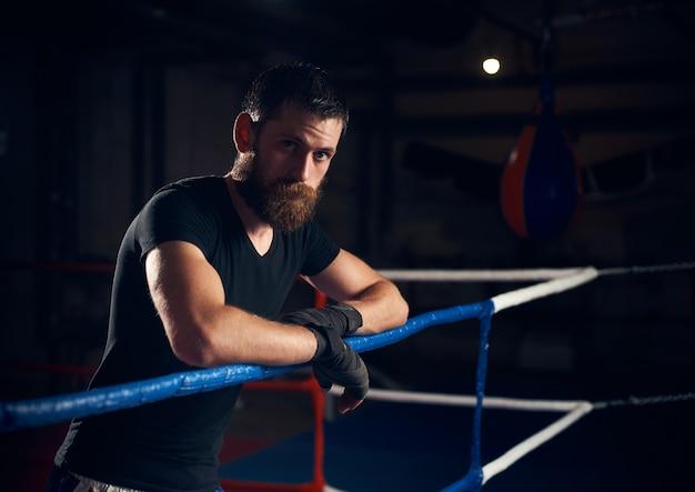 Porträt des schönen kickboxers im ring am gesundheitsclub