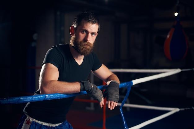 Porträt des schönen kickboxers im ring im fitnessstudio