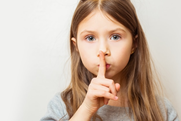 Porträt des schönen kindermädchens mit finger auf den lippen