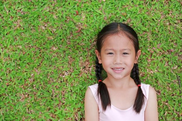 Porträt des schönen kleinen asiatischen kindermädchens mit dem haar mit zwei pferdeschwänzen, das auf rasen des grünen grases liegt.