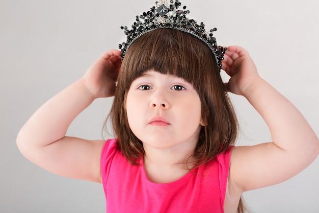 Porträt des schönen kleinen brünetten mädchens im rosa prinzessinkleid mit einer krone auf einem grauen hintergrund. süßes baby