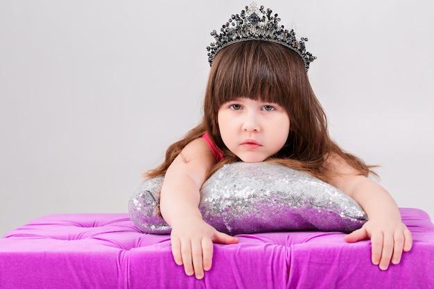 Porträt des schönen kleinen brünetten mädchens im rosa prinzessinkleid mit einer krone auf silbernem kissen auf einem grauen hintergrund. süßes baby
